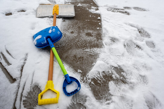 Adult and child snow shovel next to each other