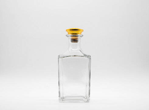 Empty glass bottle closed with big golden round cork isolated on a white background. Transparent square bottle. Front view of the vertical staying jar.