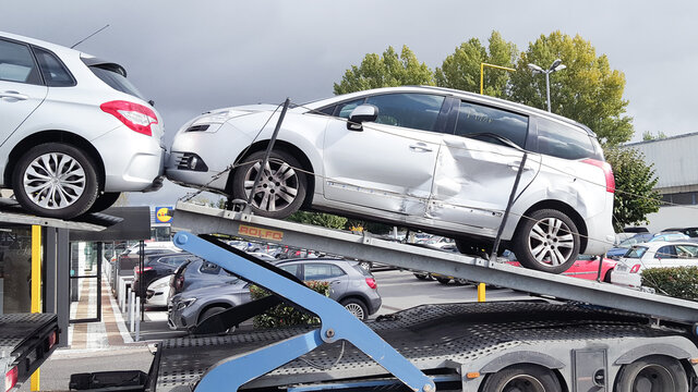 loading broken peugeot car recovered by insurance after a traffic accident on a tow truck trailer