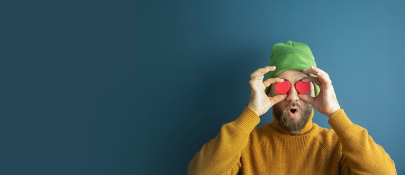 Portrait of a cheerful funny young hipster man with hearts in his eyes on a blue background. Sales, discounts, Valentine's Day and love concept.