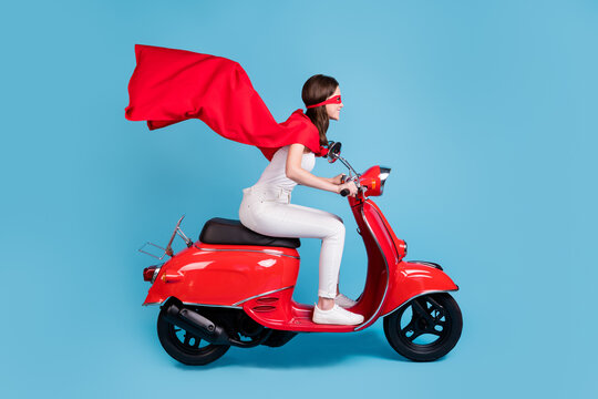 Full length profile photo of attractive hero lady drive moped wear white outfit red cloak mask isolated on blue color background
