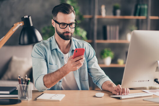 Photo portrait of man holding phone in one hand working at desk in modern industrial office indoors