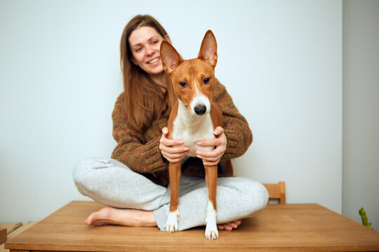 Woman with basenji dog sitting oa a table.