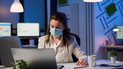 Employee with protection face mask working late at night in new normal business office to respect...
