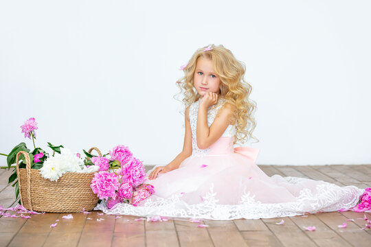 Little beautiful child girl in luxury dress with peonies in indoor white background