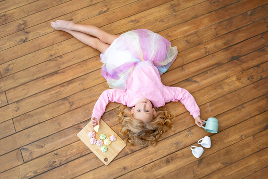 Little beautiful child girl lying on wooden floor with mugs and sweet marshmallows