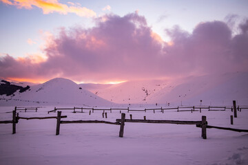 Winter sunset on the plain of castelluccio di norcia, in italy. The plain is covered with snow that reaches up to the fence. The warm sunset are reflected in the snow together with the colored clouds.