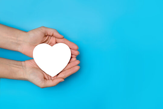 hold a heart in your hands close-up on a blue background copy space. the cardiologist