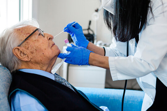 Nurse performing a coronavirus pcr test on an elderly man in his home