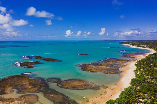 Beautiful view of the sea and beach on a sunny day and blue sky with few clouds. Coral reefs visible underwater at Praia do Espelho, Bahia, Brazil. Post pandemic travel destination.