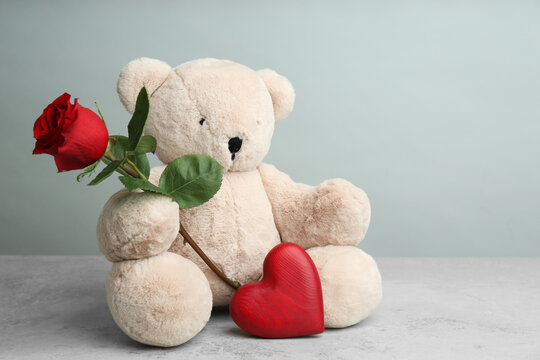 Cute teddy bear with heart and red rose on light grey stone table. Valentine's day celebration