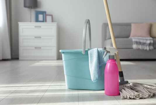 Bucket, mop and bottle of cleaning product on floor indoors. Space for text
