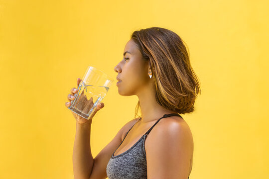 Healthy, smiling young woman with a glass of water on a yellow background