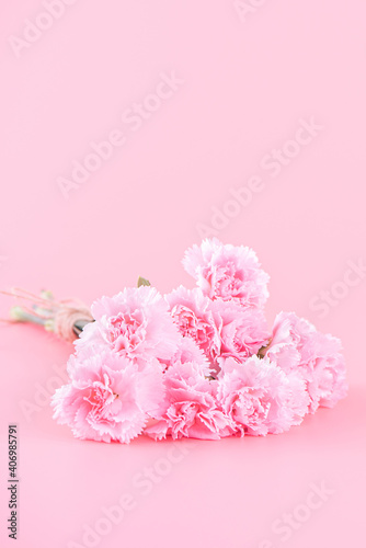 Mother's Day holiday gift design concept, pink carnation flower bouquet with greeting card, isolated on light pink background, copy space.