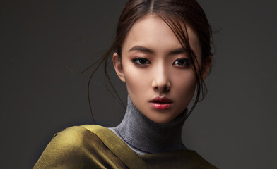 Beautiful Asian woman in a green shawl. Beauty of mysterious Chinese girl with flowing hair. Fashion, clothing and cosmetics - fototapety na wymiar