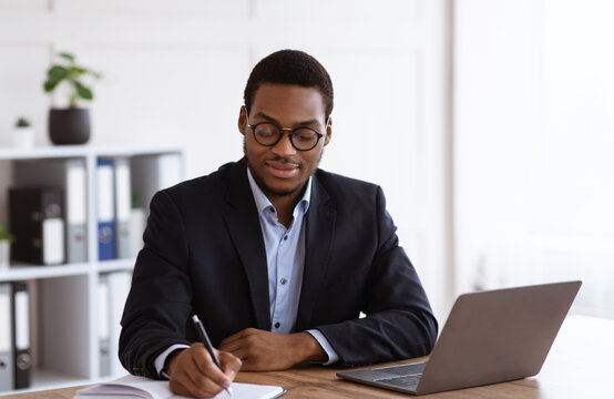 Enthusiastic black businessman planning his day in office