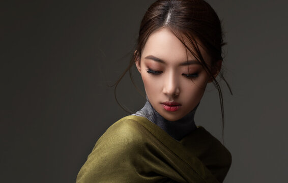 Beautiful Asian woman in a green shawl. Beauty of mysterious Chinese girl with flowing hair. Fashion, clothing and cosmetics