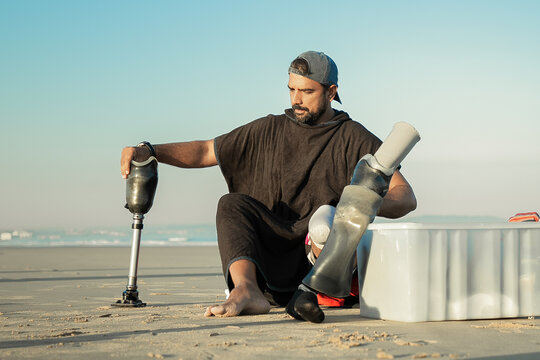 Serious male surfer sitting on sand near surfboard and changing below-knee prosthesis. Front view. Artificial limb and outdoor activity concept