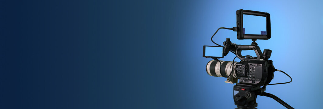 Professional video camera filming on dark abstract blue background, broadcasting banner with copy space