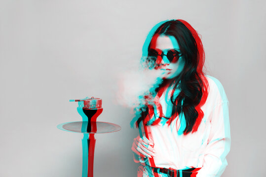 An attractive woman in a hipster image smokes a hookah, sheesha and enjoys smoking. Black and white with 3D glitch virtual reality effect