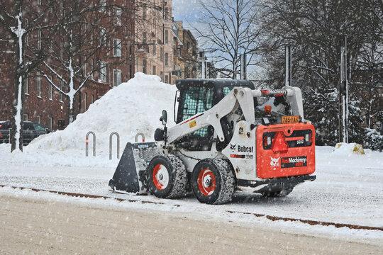 Bobcat Skid Steer Loader Snow Removal in winter snowfall.