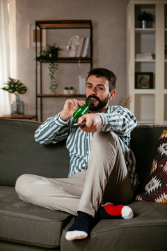 Young man at home. Man sitting in living room watching movie and drinking beer.