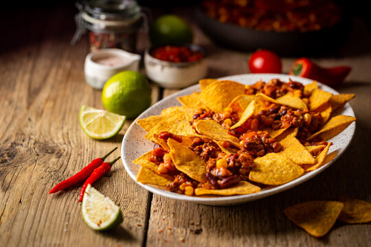 Delicious plate of yellow corn nachos chips with cheese, minced meat and red hot spicy salsa over wooden table