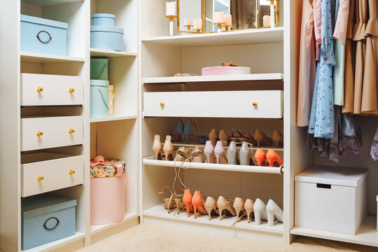 Large wardrobe with stylish women's clothing, shoes, accessories and boxes. Organization of storage space and fashion concept