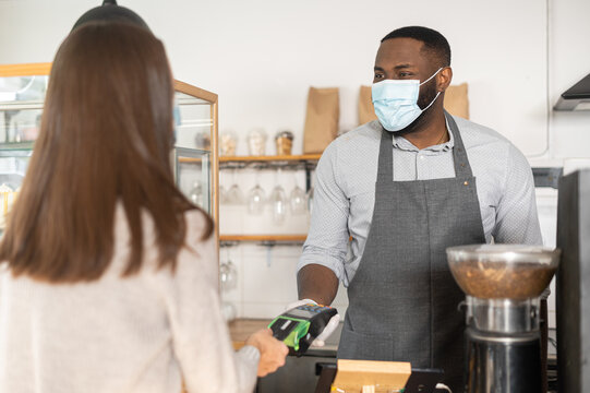 Back view a female customer making contactless payment with a credit card, an African waiter stands behind counter in mask and gloves and holds a terminal. Protective measures during quarantine covid