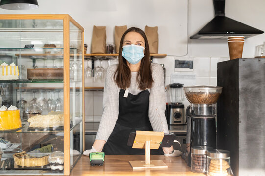 A female bakery owner wearing mask and gloves stands behind the counter, waiting for customers. A young entrepreneur, bakery staff, waitress during quarantine lockdown