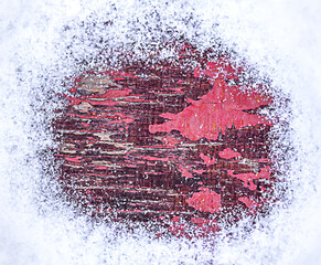 Frame of snow on red wooden background, top view with space. An old natural wood.