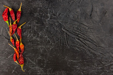 Hot red chili pepper dry lies on a black background Top view