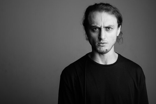 Young handsome man wearing black shirt against gray background