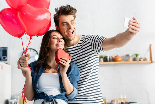 happy man and woman taking selfie on valentines day