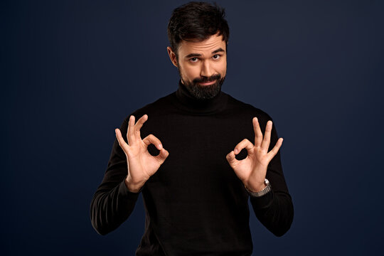 Guy knows how make perfection.Confident good-looking charming bearded man showing okay, ok signs and smirk as arranging best new year party ever, encourage everything be great, Pacific Blue background