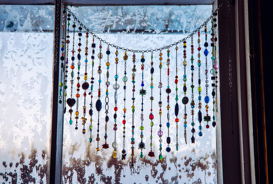 Handmade sun catcher with crystals and beading window curtains hanging on winter frosty window.
