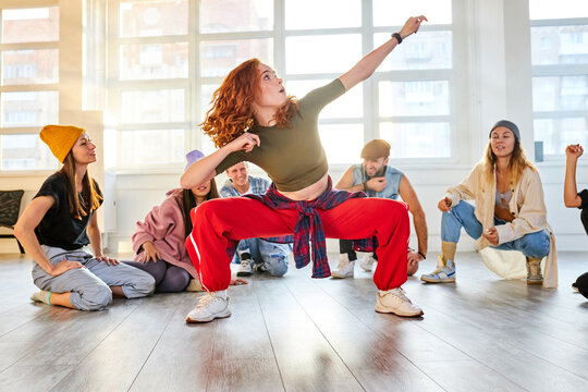 female dancer show her abilities in the studio, while other look at her moves. sportive youth gathered to train