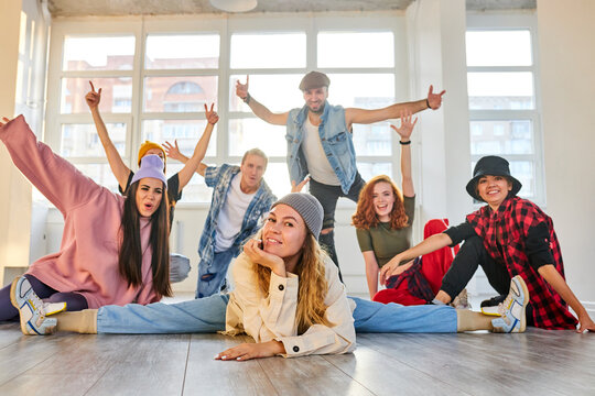 woman in casual wear with colleagues dancers posing at camera in studio, sit on the floor looking at camera. party, dance, youth concept