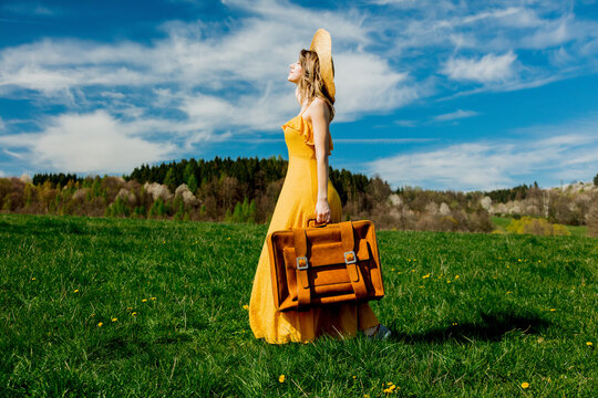girl in yellow dress and suitcase on mountain meadow with dandelions