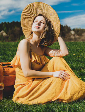 girl in yellow dress and suitcase sitting on mountain meadow with dandelions