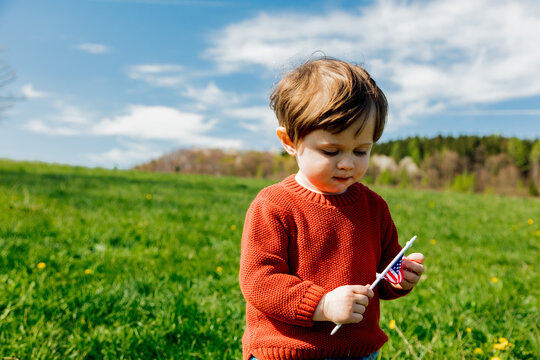 Little toddler boy in red sweater on spring time meadow