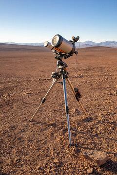 An amateur telescope setup equipment over the sand at Atacama Desert. Preparing a stargazing night during sunset in an amazing arid scenery under a blue sky