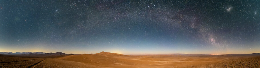 An amazing panoramic view of the Milky Way above Atacama Desert vast sand fields. An awe night sky view with our galaxy arm creating an arch in between the stars. An idyllic and motivational scenery.