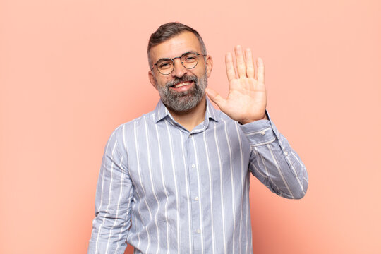 adult handsome man smiling happily and cheerfully, waving hand, welcoming and greeting you, or saying goodbye