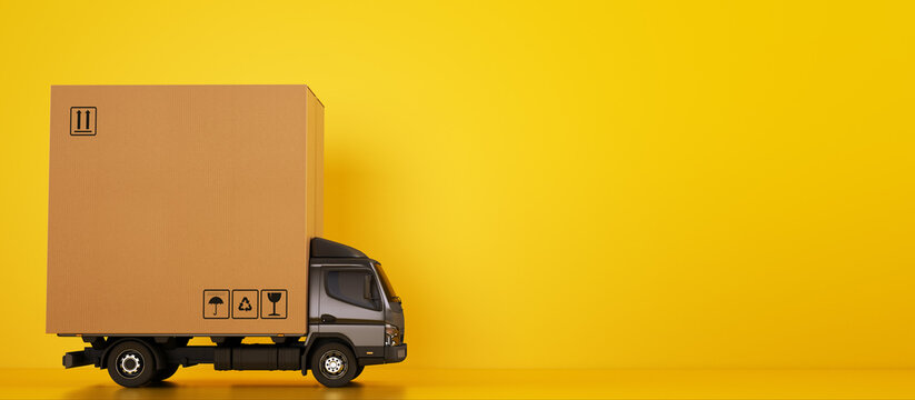 Big cardboard box package on a grey truck ready to be delivered on yellow background