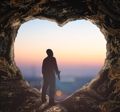Worship God concept: Silhouette human standing on cave of heart against blurred mountain sunrise background