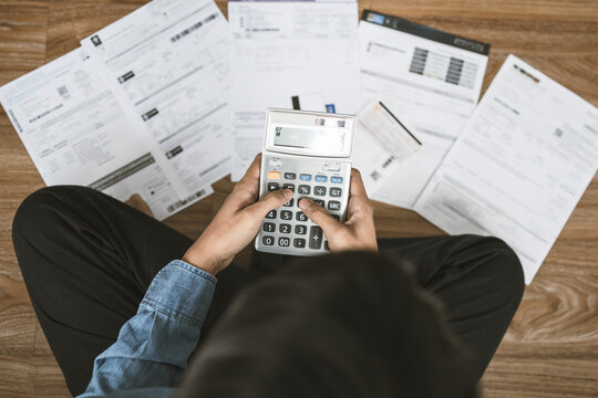 Top view man sitting on the floor stressed and confused by calculate expense from invoice or bill, have no money to pay thinking of taking the house to mortgage causing debt, bankruptcy concept.