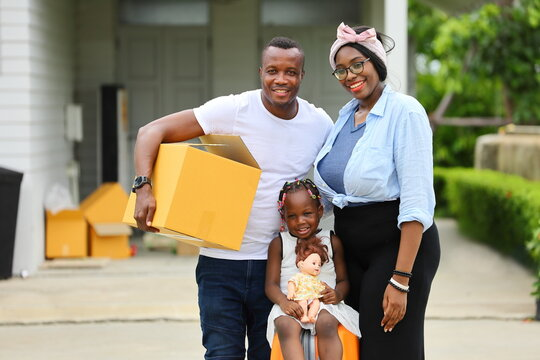 African American family is moving in to a new house with father holding cardboard box along with suitcase and baggage with happy smile