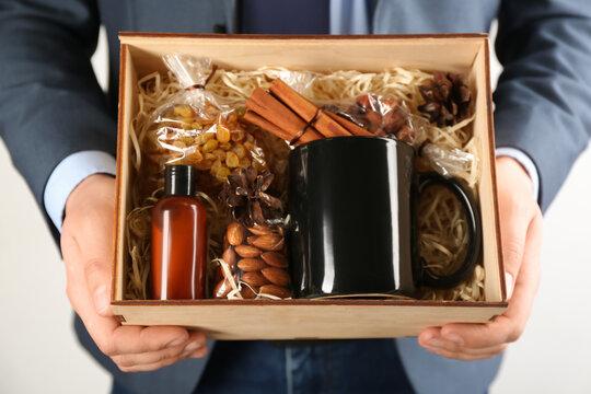 Man holding box with stylish craft gift set on light grey background, closeup