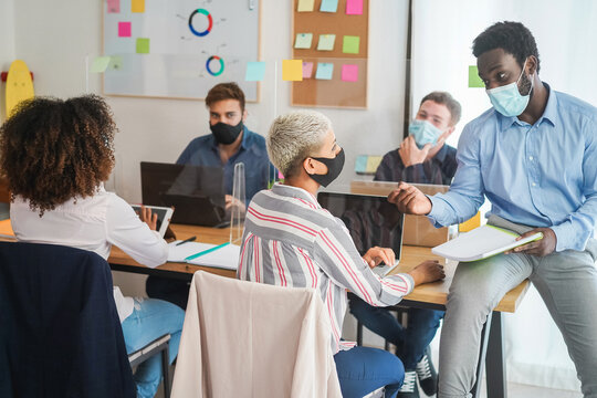 Young people working inside coworking office while wearing protective masks - Business and coworkers during coronavirus outbreak - Focus on african man face